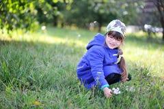 Nice little girl in blue coat picks up flowers Stock Photo
