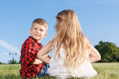 Nice little girl and boy sitting backwards Royalty Free Stock Image