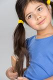 Nice little girl combing hair. Royalty Free Stock Photos