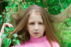 Nice little girl costs near a tree Stock Photos