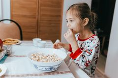 Nice little girl dressed in pajama is eating popcorn in kitchen royalty free stock photography