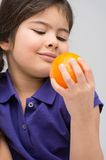 Nice little girl holding orange. Royalty Free Stock Image