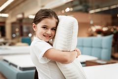 Nice little girl hugs pillow in store of orthopedic mattresses. Testing softness of pillow. Check softness of orthopedic pillow Royalty Free Stock Photography