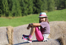 Nice little girl with long hair over hay bale in the countryside Royalty Free Stock Photography