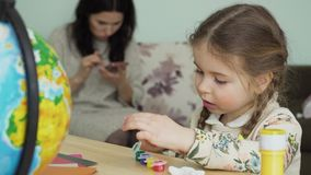 Nice little girl paints a clay craft sitting at table at home. Her mother is messaging with friends on phone at blurred background. The first-grader makes stock video