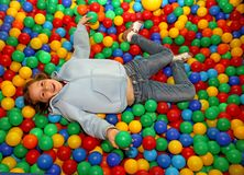 Nice little girl play dipped in colored balls of kindergarten po. Beautiful little girl play dipped in colored balls of kindergarten pool Stock Photo