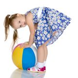 Little girl is playing with a ball. A nice little girl is playing with a big inflatable ball. The concept of a happy childhood, family recreation in nature Stock Image