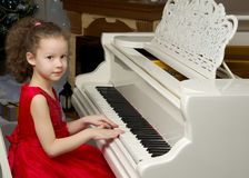 Beautiful little girl is playing on a white grand piano. A nice little girl is playing on a big white piano. The concept of musical and aesthetic education of a royalty free stock photos
