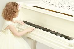 Beautiful little girl is playing on a white grand piano. A nice little girl is playing on a big white piano. The concept of musical and aesthetic education of a Stock Images