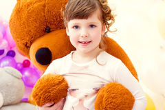 Nice little girl posing in arms of big teddy bear Stock Image