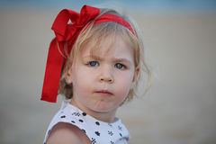 Nice little girl posing near sea wearing a red ribbon Royalty Free Stock Photography