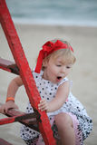 Nice little girl posing near sea wearing a red ribbon, smiling up the ladder baby girl Royalty Free Stock Images