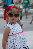 Nice little girl posing with sunglasses and a red ribbon Stock Photography