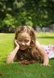 Nice little girl resting on a green grass Royalty Free Stock Photos
