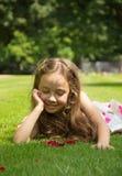 Nice little girl resting on a green grass. Pretty little girl resting on a green grass royalty free stock photos