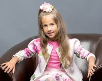 A little girl is sitting on a leather chair. A nice little girl is sitting on a leather chair. The concept of family happiness and home comfort Royalty Free Stock Photos