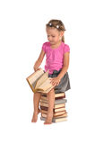 Nice little girl sitting on stack of books Stock Photo