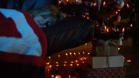 A little girl is sleeping on a sofa under a rug at a Christmas tree at night. A nice little girl is sleeping on the couch under a striped red white plaid in the stock video footage