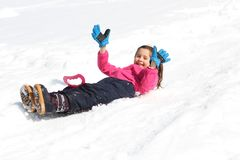 Nice little girl slips down on snowy mountain Stock Image