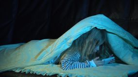 A little girl in a striped pajamas at night in her room uses a smartphone. A nice little girl in a striped pajamas at night in her room is lying under a blanket stock footage