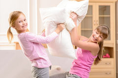 Nice little sisters fighting with pillows Stock Image