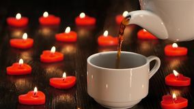 Nice little things in life - cup of coffee by candlelight. Nice little things in life, cup of coffee by in a lot of candles in the shape of heart, brown wooden stock video