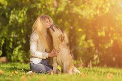 Close up portrait of beautiful long haired girl with her Labrador Retriever dog in the park stock photo