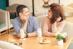 Nice looking couple in cafe. Date in cafe. Lovely couple in cafe with stylish interior. Man and women having delicious coffee drinks. They chatting and smiling Stock Images