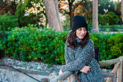 Nice looking girl posing in a green park. Nice looking girl with dark hair, black hat and grey coat posing in the park - green background Stock Image