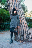 Nice looking girl posing next to a tree in the park. Nice looking girl with dark hair, black hat and grey coat posing next to a tree in the park Stock Images