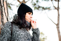 Nice looking girl smoking a sigarette in a park - inhaling Stock Photography