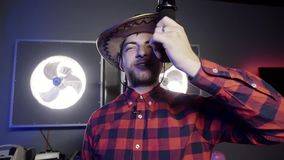 Nice-looking grey eyed bearded man with mexican hat holds microphone and sings. Nice looking young bearded grey eyed man vlogger put on stylish mexican hat and stock video