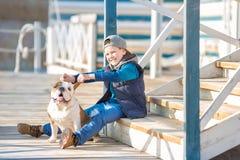 Nice looking handsome boy on beach with bulldog Stock Photo