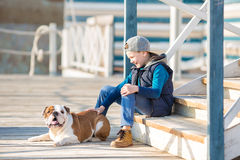 Nice looking handsome boy on beach with bulldog Royalty Free Stock Image