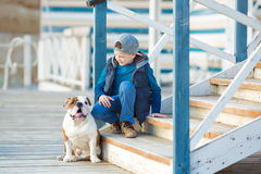 Nice looking handsome boy on beach with bulldog Royalty Free Stock Photography