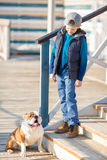 Nice looking handsome boy on beach with bulldog Stock Photography