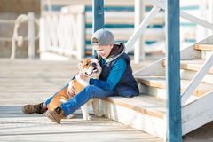 Nice looking handsome boy on beach with bulldog royalty free stock photo