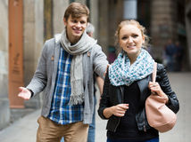 Nice-looking male student chasing pleased girl on outdoor date Stock Photography