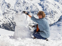 Girl snowman mountains Royalty Free Stock Images