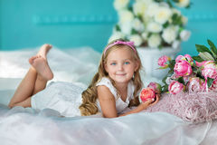 Nice looking young girl lady in cute dress sitting on a sofa with flowers in white stylish dress. stock photography
