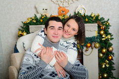 Nice love couple sitting on carpet in front of fireplace Royalty Free Stock Photos