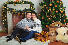 Nice love couple sitting on carpet in front of fireplace Stock Photography