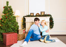 Nice love couple sitting on carpet near the fireplace. Woman and man celebrating Christmas Royalty Free Stock Photography
