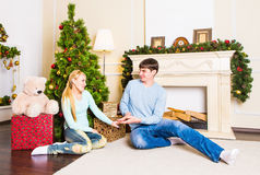 Nice love couple sitting on carpet near the fireplace. Woman and man celebrating Christmas Stock Image