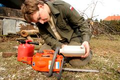 Nice lumberjack. Young woodcutter refuelling chainsaw Royalty Free Stock Photo