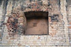 Nice mönstrade stentegelstenväggen med ett fyrkantigt fönster i Prague ideal för bakgrundsbild arkivbild
