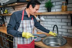 Nice man in apon stand in kitchen and touch sink. He hold plate. Guy wear washing gloves. royalty free stock photos