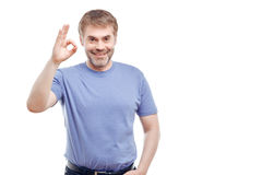 Nice man expressing positivity. Pleasant smiling man holding hand raised and showing ok while standing isolated on white background royalty free stock photos