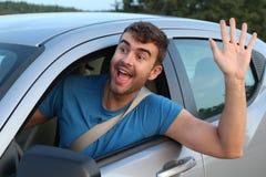 Nice man greeting someone while driving royalty free stock photos