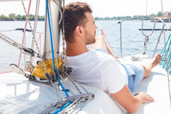 Nice man lying on yacht deck Royalty Free Stock Images